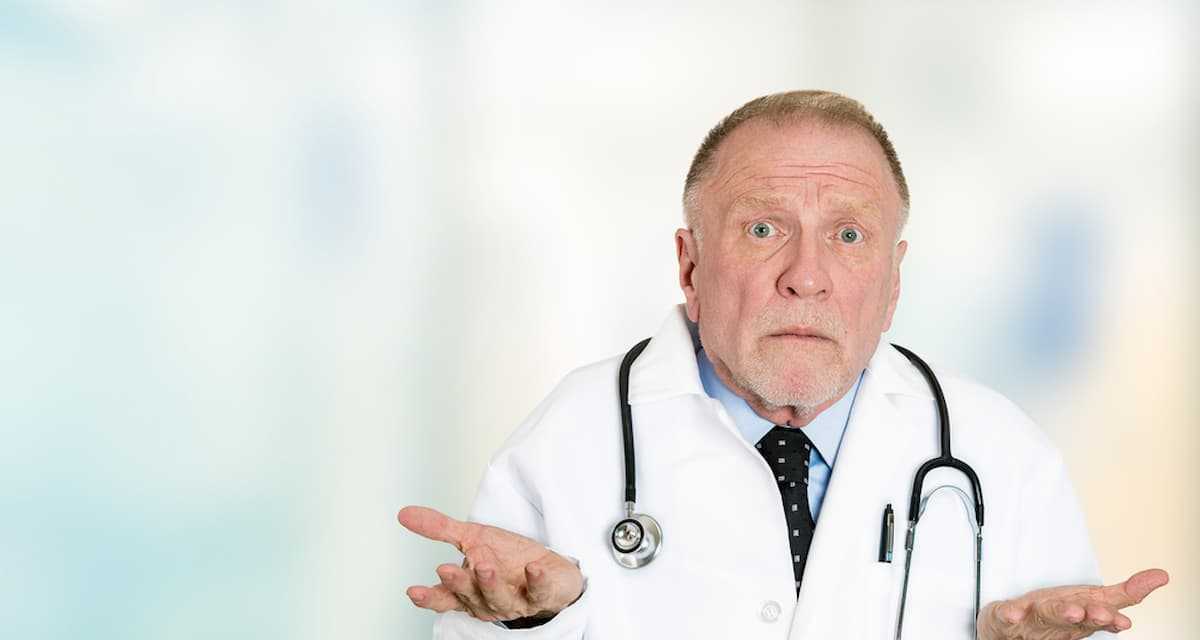 Closeup portrait clueless senior health care professional doctor with stethoscope, has no answer, doesnt know right diagnosis standing in hospital hallway isolated clinic office windows background.