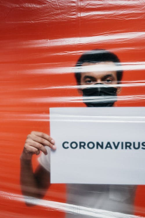 college student holding coronavirus (COVID-19) sign with blood red background