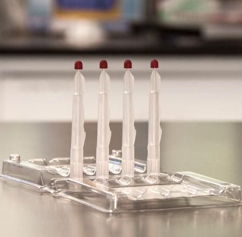 Die Mitra®-Schale mit 4 Probenentnahmespitzen in einem Laborumfeld
