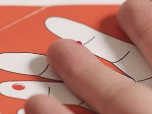 Nahaufnahme eines Fingers mit einem Bluttropfen, der sich nach dem Einstechen der Lanzette bildet