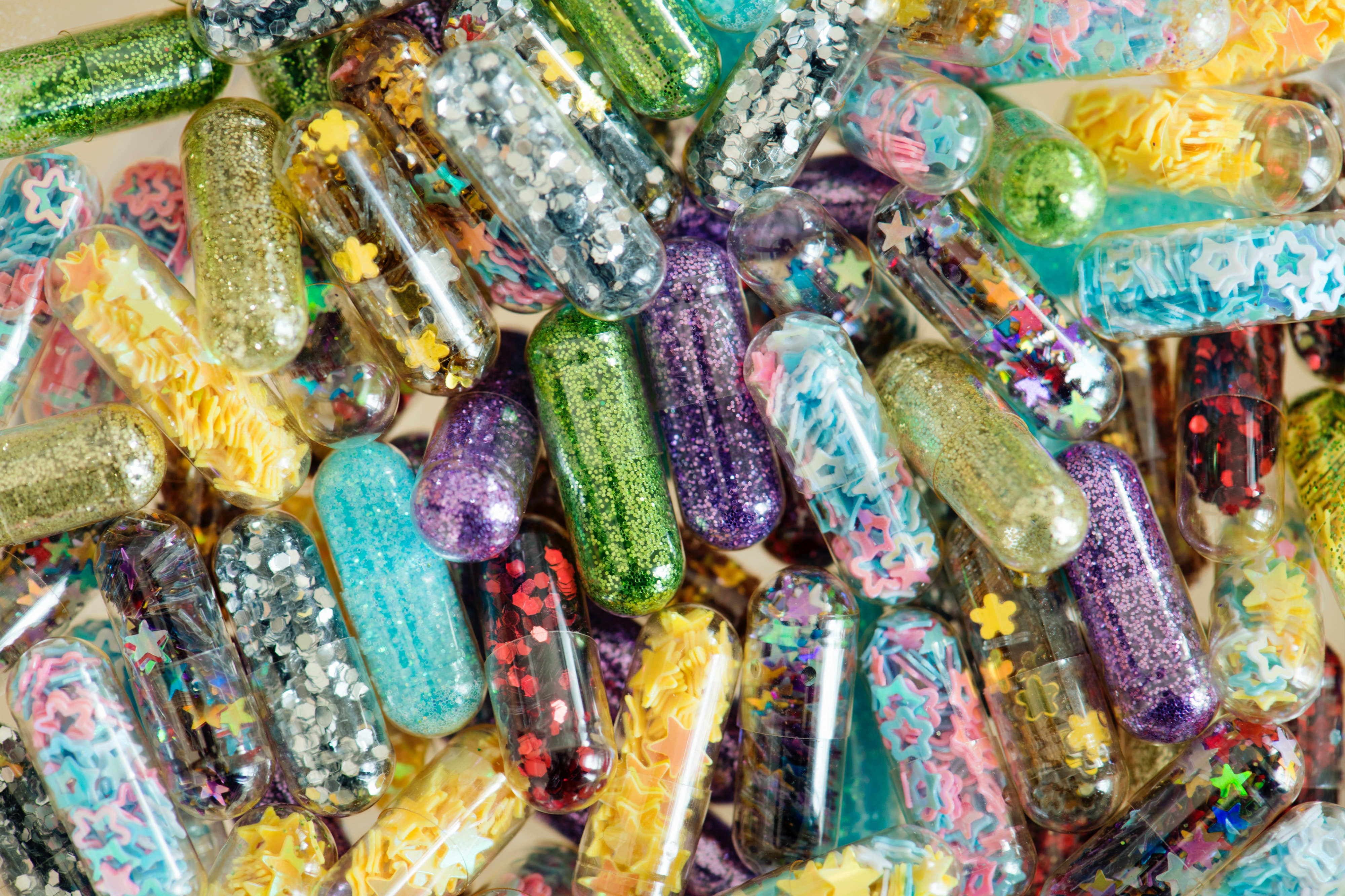 a pile of translucent pills filled with glitter and confeti