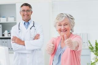 A happy elderly patient smiles in her doctors office.